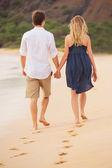 Romantický šťastný pár, chůze po pláži při západu slunce. usmíval se, holdin — Stock fotografie