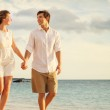 Young couple in love walking on the beach at sunset — Stockfoto