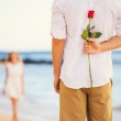 Romantic Young Couple in Love, Man holding surprise rose for bea — Stock Photo #36703641