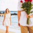 Romantic Young Couple in Love, Man holding surprise bouquet of r — Stock Photo #36703975