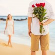 Romantic Young Couple in Love, Man holding surprise bouquet of r — Stock Photo #36703979