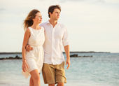 Young couple in love walking on the beach at sunset — Stock Photo