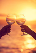 Man and woman clanging wine glasses with champagne at sunset dra — Stock Photo