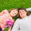 Stock Photo: Happy mother and daughter relaxing outside on green grass. Spend