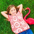 Smiling little girl lying on green grass with pink flamingo — Stock Photo #37458257