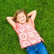 Smiling little girl lying on green grass — Stock Photo