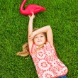 Smiling little girl lying on green grass with pink flamingo — Stock Photo #37458315