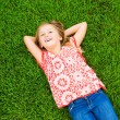 Smiling little girl lying on green grass — Stock Photo #37458537