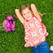 Smiling little girl lying on green grass with flowers — Stock Photo #37458585