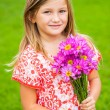 Portrait of a smiling cute little girl with flowers — Stock Photo