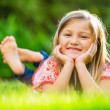 Portrait of a smiling little girl lying on green grass — Stock Photo #37459071