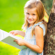 Stock Photo: Little girl reading book outside