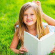 Cute little girl reading book outside on grass — Stock Photo