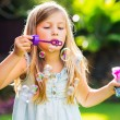 Cute little girl blowing soap bubbles — Stock Photo #37459619