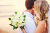Bride holding bouquet of white flowers gazing at the ocean into — Stock Photo