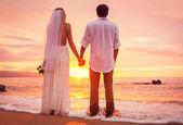 Novia y novio, disfrutando de increíble puesta de sol en un hermoso tropical — Foto de Stock