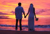 Bruid en bruidegom, genieten van geweldige zonsondergang op een mooie tropische — Stockfoto
