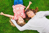 Happy mother and daughter relaxing outside on green grass. Spend — Stock Photo