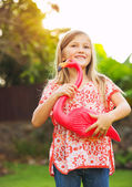 Portrait of cute little girl outside with pink flamingo — Stock Photo