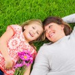 Mother and daughter lying together outside on grass — Stock Photo #37800469
