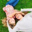 Stock Photo: Mother and daughter lying together outside on grass
