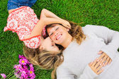 Mother and daughter lying together outside on grass — Stock Photo