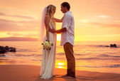 Just married couple on tropical beach at sunset — Stock Photo