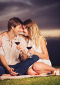 Couple drinking glass of wine on romantic sunset picnic — Stock Photo