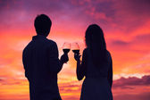 Silhouette of couple drinking wine at sunset — Stock Photo