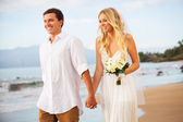 Just married couple walking on the beach at sunset — Stock Photo
