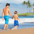 Happy father and son walking together at beach — Stock Photo