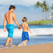 Stock Photo: Happy father and son walking together at beach