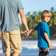 Stock Photo: Happy father and son walking together on beach, carefree hap