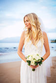 Beautiful bride in wedding dress with flowers at sunset on beaut — Stock Photo