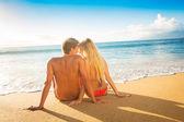 Casal assistindo o pôr do sol de férias de praia tropical — Fotografia Stock