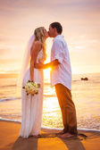 Married couple, bride and groom, kissing at sunset on beautiful — Stock Photo