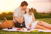 Пара наслаждается романтическим закатом пикник — Стоковое фото