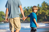 Happy father and son walking together on the beach, carefree hap — Stock Photo