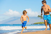 Happy father and son playing and running together at beach — Stock Photo
