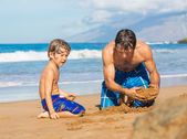 Father and son playing together in the sand on tropical beach — Stock Photo