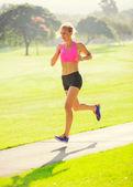 Młoda kobieta, jogging, działa na zewnątrz — Zdjęcie stockowe
