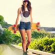 Beautiful young woman with a skateboard — Stock Photo #40057281
