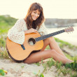 Beautiful young woman playing guitar on beach — Stock Photo