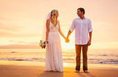 Bride and groom on beach at sunset — Stock Photo