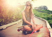 Beautiful young woman with a skateboard — Stock Photo