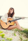 Beautiful young woman playing guitar on beach — Stockfoto