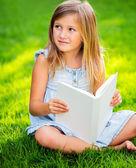 Adorable little girl reading book — Stock Photo