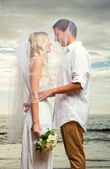 Bride and groom at tropical beach — Stock Photo