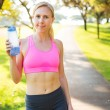 Athletic young woman runner drinking water — 图库照片
