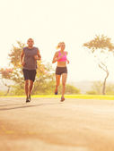 Couple running in the park at sunrise — Stock Photo